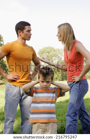 A young boy closes his ears as his parents argue. - stock photo