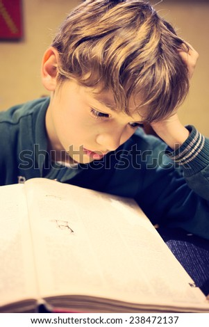 A young boy concentrating on homework. - stock photo