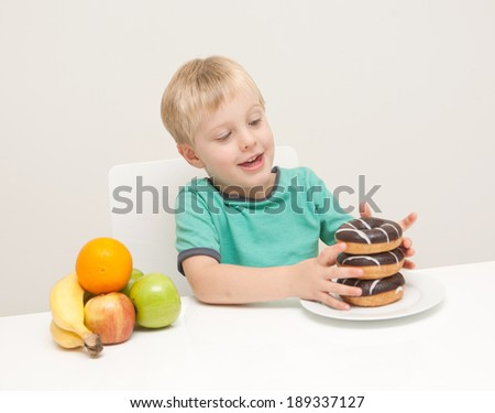 A young boy considers whether he will have a unhealthy donuts or some healthy fruit.  The child is photographed against a white background - stock photo