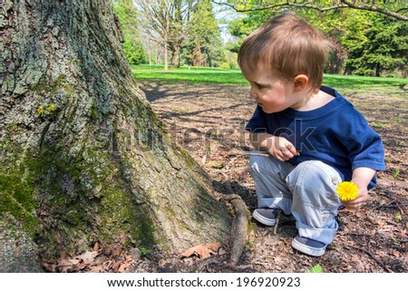 A young boy crouches near a tree looking at the tree while holding a dandelion flower in one hand and a small twig in the other.  - stock photo