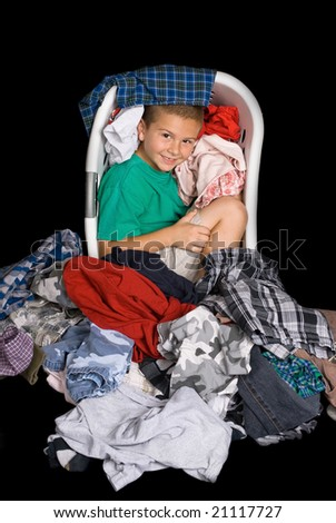 A young boy curls up in a warm clothing basket full of freshly dried clothes. - stock photo