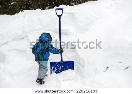 A young boy digs in the deep snow with shovel chipping away at a snowbank during the winter season.  Room for copy space.  - stock photo