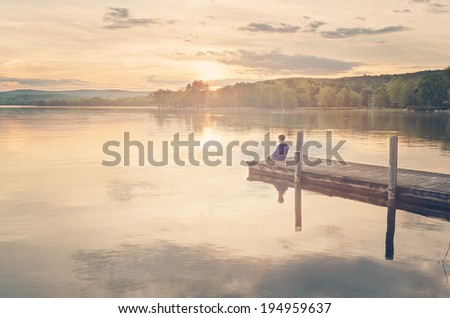 a young boy dipping his feet in a lake at sunset - stock photo