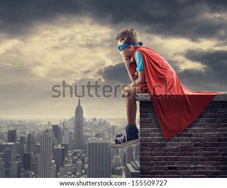 A young boy dreams of becoming a superhero. - stock photo