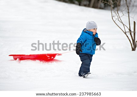 A young boy dressed for cold weather pulls a red sled by a rope along in the snow  - stock photo