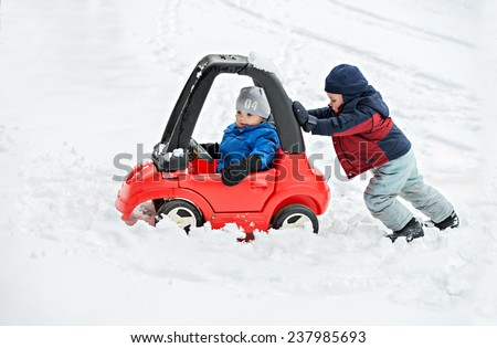 A young boy dressed for cold weather sits in a red toy car stuck in the snow during the winter season.  His older brother helps by giving the car a push from behind.  - stock photo