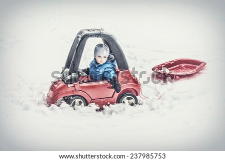 A young boy dressed for cold weather sits in a red toy car stuck in the snow pulling behind a red sled during the winter season.  Filtered for a retro, vintage look.  - stock photo