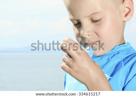 A young boy having a asthma problem using inhaler outside - stock photo
