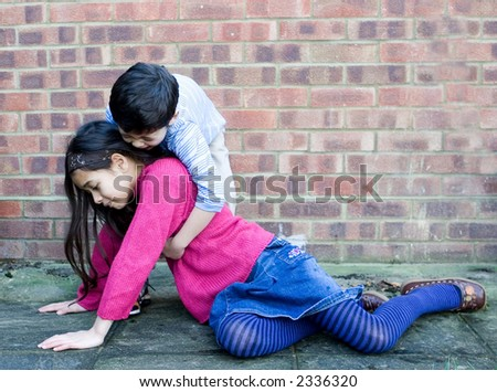A young boy helping his sister up after she slips over. - stock photo