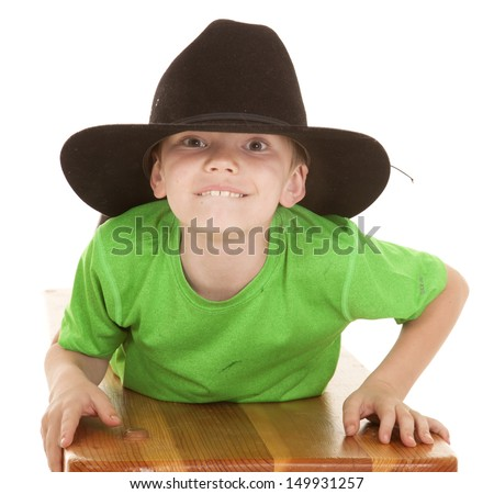 a young boy in a big cowboy hat laying and looking. - stock photo