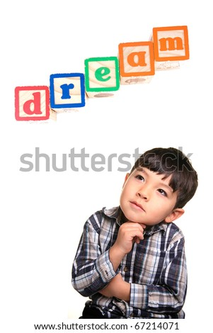 A young boy in a day dreaming pose under the word blocks. - stock photo