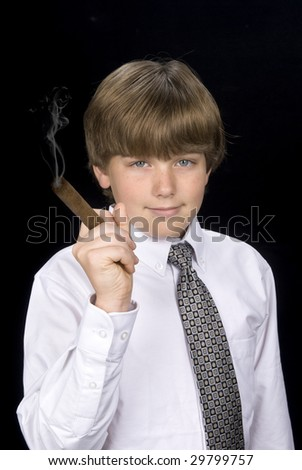 A young boy in a dress shirt and tie smokes a cigar as if living a high society lifestyle. Good for any business inference and for health smoking issues. - stock photo