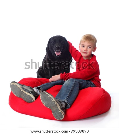 A young boy in red, on a red bean bag chair, with his arm around a black lab. - stock photo
