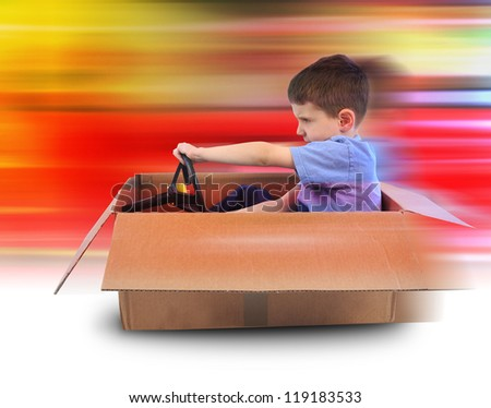 A young boy is driving in a cardboard box with red speed lines in the background. Use it for a shipping or imagination concept. - stock photo