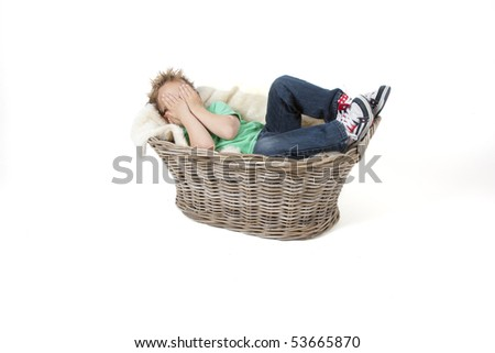 A young boy is hiding his face - stock photo