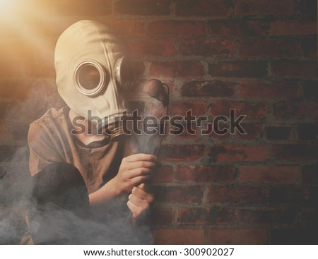 A young boy is holding a dead flower against a brick wall with a gas mask and dangerous gas in the air for a global warming or destruction concept. - stock photo