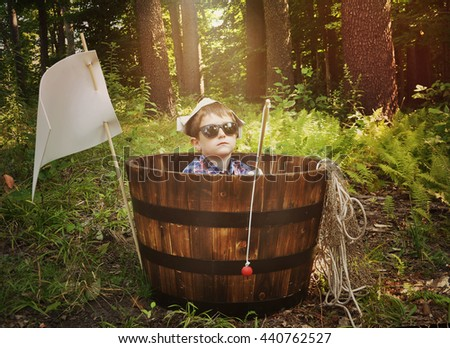 A young boy is relaxing in a wooden boat barrel with a fishing pole toy in the woods for a imagination, activity or recreation concept. - stock photo