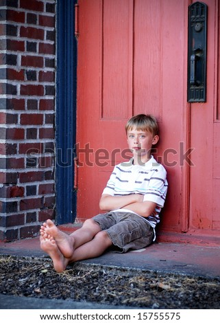 A young boy is sitting against a red wall.  He is looking at the camera and folding his arms across his chest.  Vertically framed shot. - stock photo