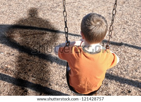 A young boy is sitting on a swing set and looking at a shadow figure of a man or bully at a playground. Use it for a kidnap, defense or safety concept. - stock photo