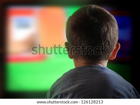 A young boy is watching a television screen with his back for a tv effect on children or a communication concept. - stock photo