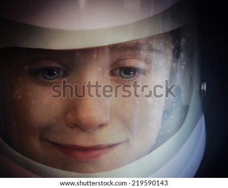 A young boy is wearing an astronaut helmet and looking into space with stars for an education or imagination concept. - stock photo