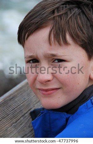 A young boy looking concerned. - stock photo