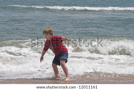 A young boy playing at the seashore. - stock photo