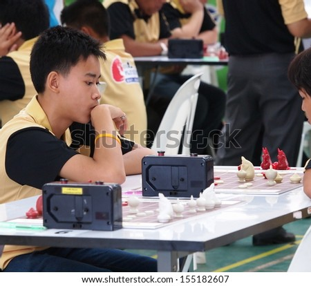 a young boy playing Thai chess, a type of chess playing in Thailand and surrounding nations,  in a local chess competition in Khon Kaen Thailand September 2013 - stock photo