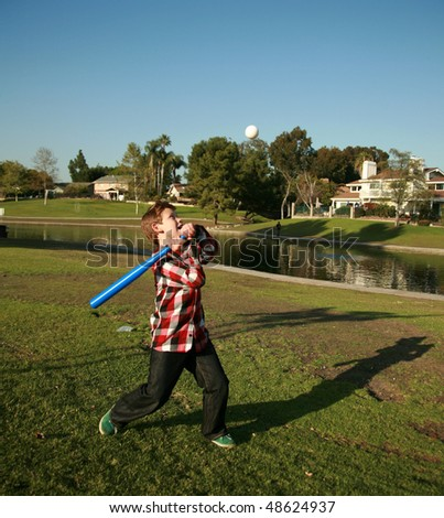 a young boy plays baseball in a park - stock photo