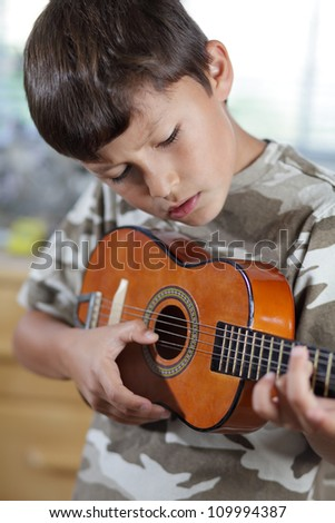 A young boy plays his guitar or ukulele - stock photo