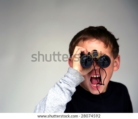 a young boy points at You the Viewer while looking through binoculars with low depth of field focus on his finger - stock photo