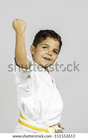 A young boy punching up dressed in a karate uniform. - stock photo