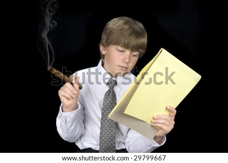 A young boy reads his notepad while smoking a cigar.  Image can be used for any business inference or smoking issues.  Shot against a black backdrop. - stock photo