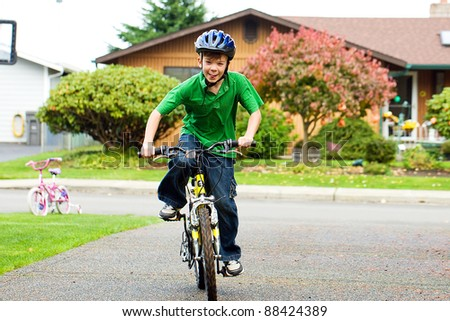 A young boy riding his bike on a driveway wearing a helmet. - stock photo