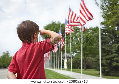 A young boy salutes the flags of a Memorial Day display along a small town street  - stock photo