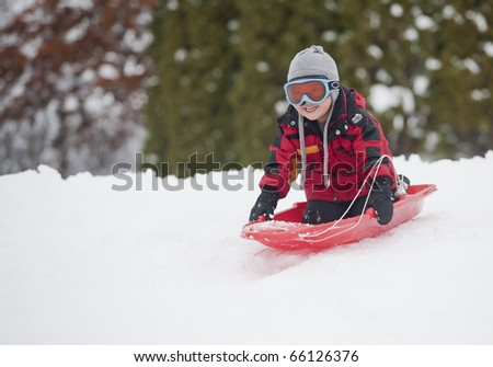 A young boy shows his excitement sledding down a hill in winter. - stock photo