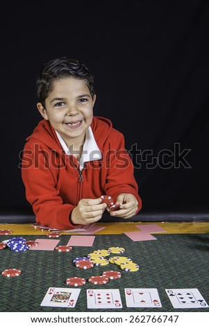 A young boy sitting at a poker table gambling playing cards with a black background - stock photo