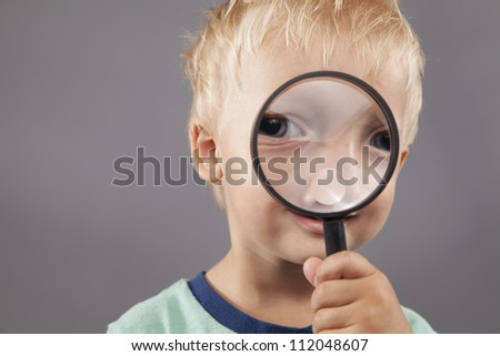 A young boy smiles and holds a magnifying glass up to his face. - stock photo