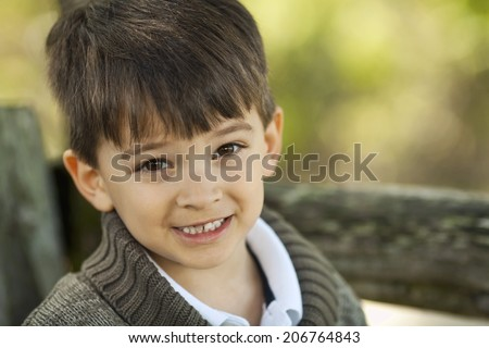 A young boy smiles at the camera. - stock photo