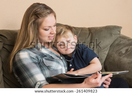 A young boy snuggles into his mother as she reads him a book. - stock photo