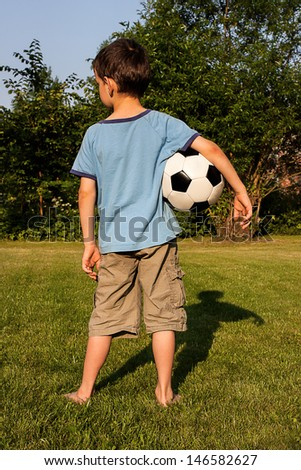 A young boy standing with a football - stock photo
