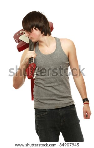 A young boy standing with his back with bass guitar on grey background - stock photo