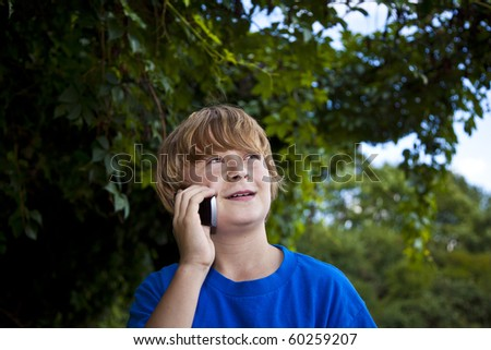 A young boy talking on a cell phone. - stock photo