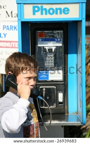 a young boy uses a public pay phone - stock photo