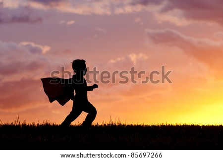 A young boy wearing a cape plays a super hero at sunset. - stock photo