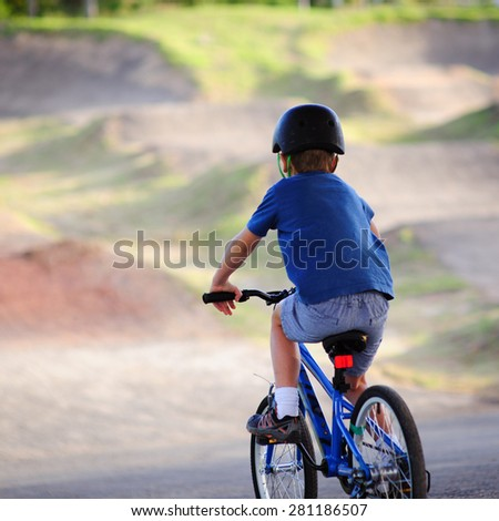 A young boy wearing a helmet and riding a bicycle ready to go down the BMX bike track on a summer day - stock photo