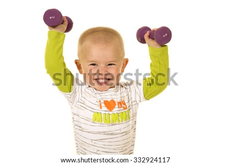 A young boy with a big smile, lifting up his weights. - stock photo