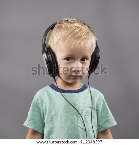 A young boy with headphones stares seriously in the camera. - stock photo