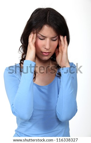 A young brunette having a headache. - stock photo