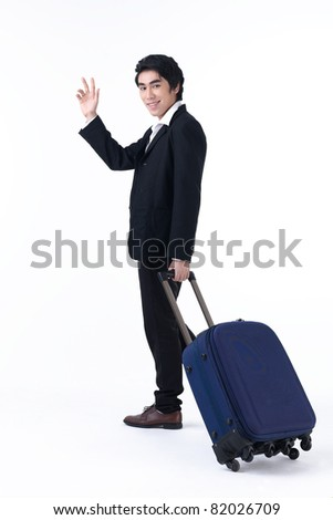 A young business man pulling luggage and waving hand - stock photo
